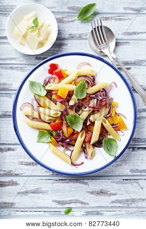 Penne with peppers, red onion and basil leaves