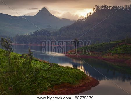 Mountain Adam's Peak at sunset with reflection in the lake. Sri Lanka