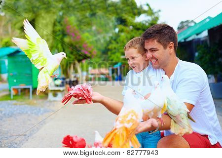 Excited Family Feeding Colorful Pigeons On Animal Farm