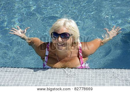 Aged Woman Is Doing Spa Exercises In Bright Blue Water Of Pool.