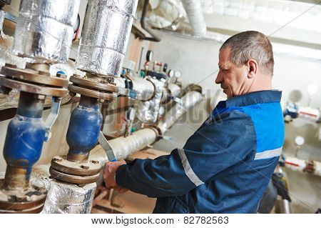 repairman plumber engineer of fire engineering system or heating system open the valve equipment in a boiler house