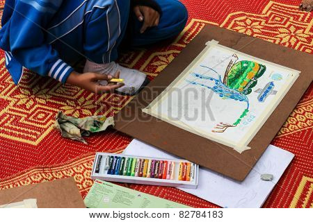 The Asian Boy Is Painting Crayon Color On Her Drawing For Drawing Contest.