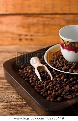 Empty Cup And Coffee Beans In Wooden Tray