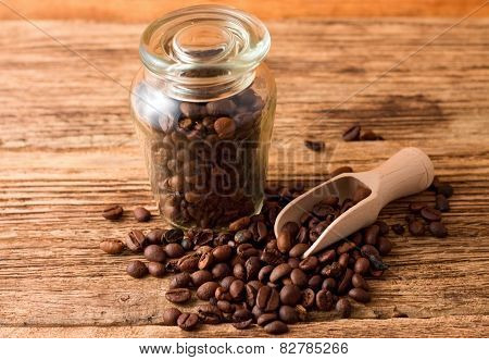 Glass Dose Full Of Coffee Beans And Wooden Spoon
