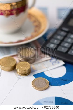 One Euro Coin And Stacks Of Other On Paper Sheets