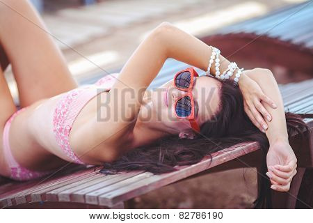 Beautiful woman sunbathing on the beach, lying on a sun lounger.