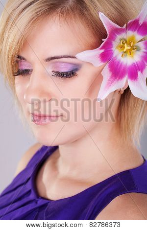Portrait of a woman with orchid flower in her hair.