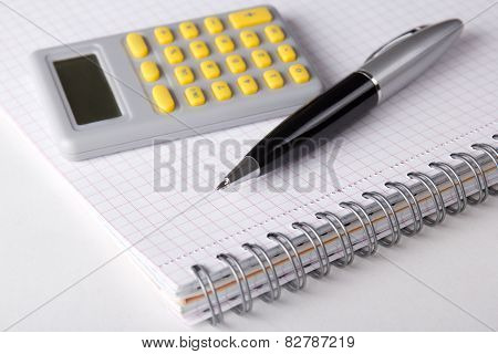 Note Book With Checked Pages, Pen And Calculator