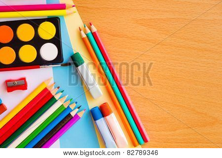 Colorful art supplies on a school desk with space for text
