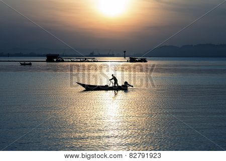 Silhouette Of Fisherman On Boat