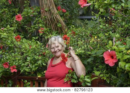 Portrait Of Aged Woman On Tropical Background With Red Flowers.