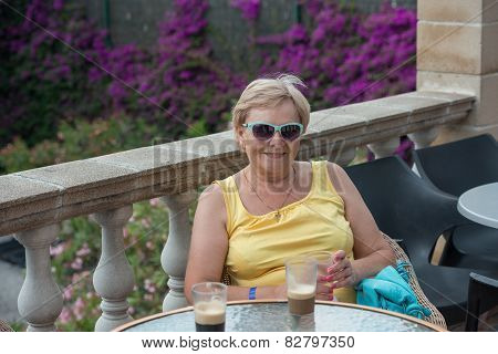 Aged Lady Is Sitting On Terrace With Glass In Hands.