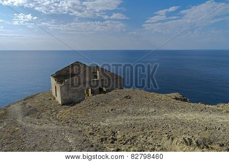 Old Ruined House On The Hillside Above The Sea.