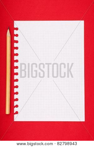 Torn blank lined notebook page with pencil on red