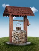 image of wishing-well  - Wishing well on grassy hill with blue sky - JPG
