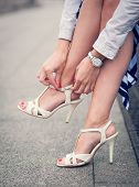 image of stiletto heels  - Legs of woman with high heels white sandals outdoor - JPG
