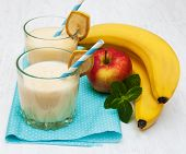 stock photo of fruit shake  - Banana smoothie and fruits on a wooden background - JPG