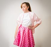 picture of teen pony tail  - Portrait of a teenage ginger girl with long hair in a pony tail wearing a pink sixties rock and roll jacket and skirt - JPG