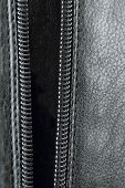 image of zipper  - Open zipper on black leather Closeup of a zipper of a leather - JPG