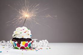 pic of sprinkling  - Cupcake with colourful sprinkles and a sparkler over a grey background - JPG