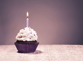picture of icing  - Chocolate Cupcake with butter cream icing purple liner and lit birthday candle - JPG