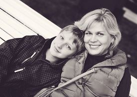 stock photo of ordinary woman  - a middle age woman and son outdoors - JPG
