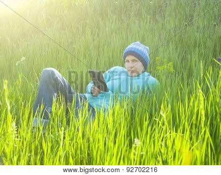 A Young Girl Looks Out The Tablet Lying On The Grass In The Field.