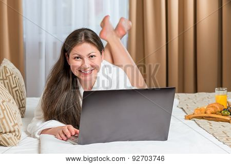 Beautiful Girl After The Shower Lying On The Bed With Laptop