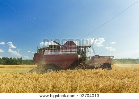 Combine Machine With Reel And The Cutter Bar Working In Farm Field