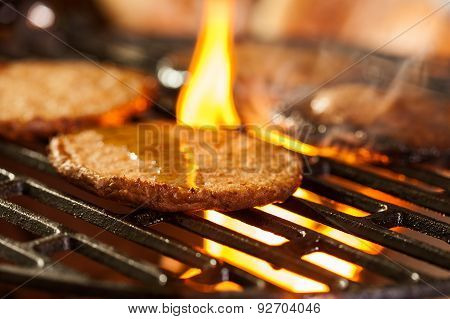 Hamburger Patties On A Grill With Fire Under