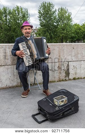 Musician Playing Accordion Near River Seine In Paris, France