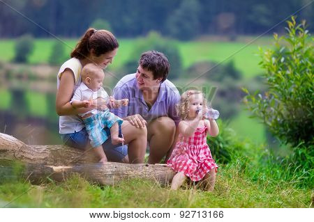 Young Family With Kids Hiking At A Lake