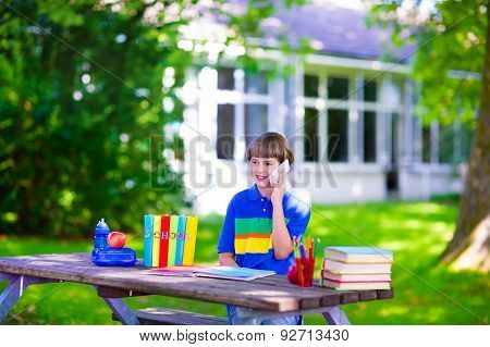 Child In School Yard Studying And Talking On The Phone