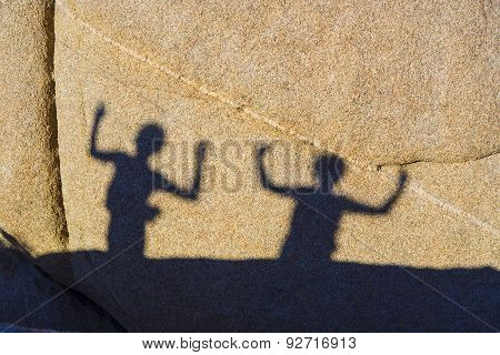 Children Playing With Shadows On A Rock