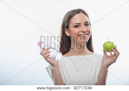 Pretty healthy girl with bottle of water and apple