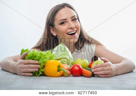Cheerful girl is sitting with healthy food