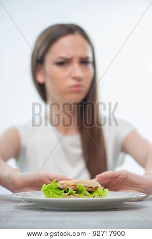 Beautiful young woman does not want to eat unhealthy food
