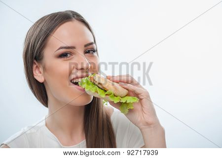 Cheerful young girl is biting unhealthy food