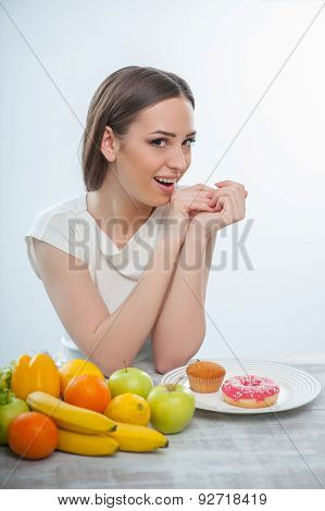 Cheerful young woman is choosing between healthy and unhealthy food