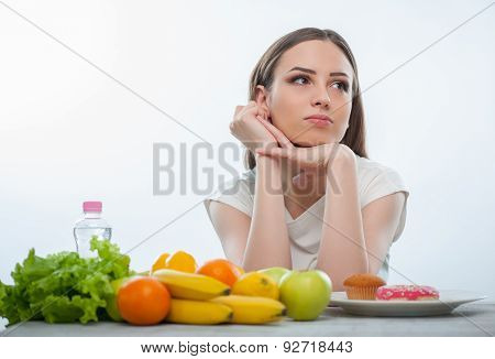 Pretty young girl is choosing between healthy and unhealthy food