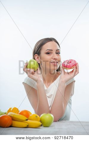 Beautiful young woman is sitting with healthy and unhealthy food