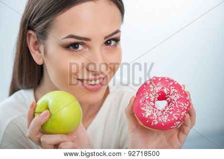 Pretty young girl with healthy and unhealthy food