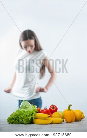 Pretty young woman is watching her figure