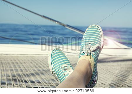 woman relaxing on a catamaran sailboat trampoline with her feet crossed