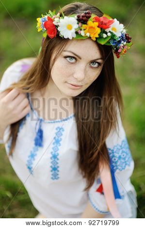 Girl With Freckles On Her Face In A Ukrainian Shirt And Floral Bouquet On The Head