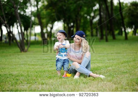 Mom And Baby Son In The Cap On A Background Of Green Grass