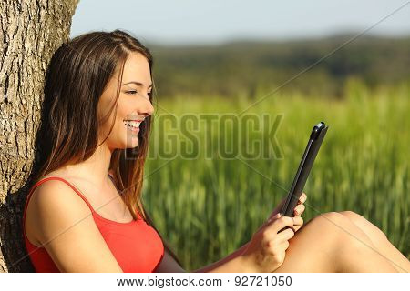 Girl Reading An Ebook Or Tablet In A Green Field