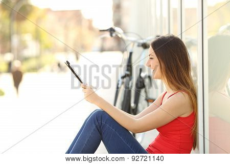Teen Girl Using A Tablet Sitting In The Street