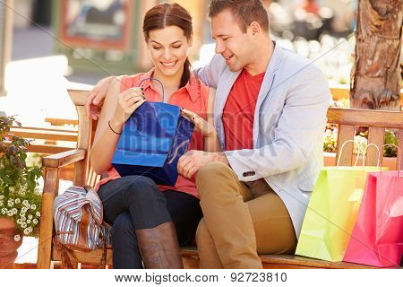 Man Giving Woman Gift As They Sit On Seat In Shopping Mall