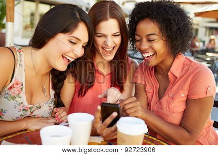 Three Female Friends Reading Text Message In Caf\x81_